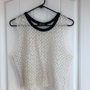 White crochet crop top with black ribbed neckline.